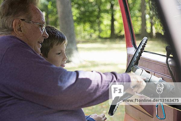 Älterer Mann zeigt Lenkrad eines Pickup-Enkels