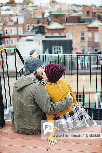 Young couple kissing on city rooftop terrace
