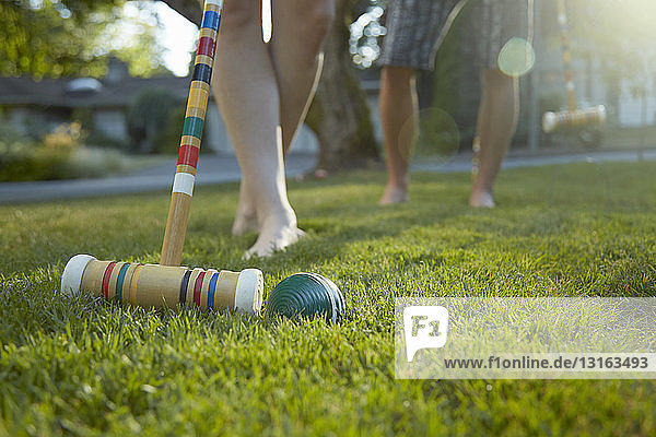 Legs and bare feet of young couple playing croquet on grass