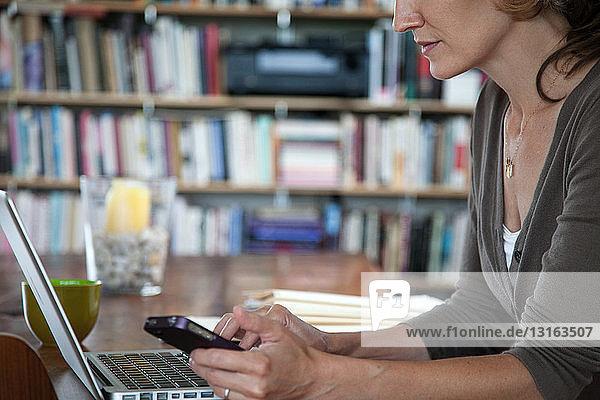 Frau schreibt SMS auf Smartphone