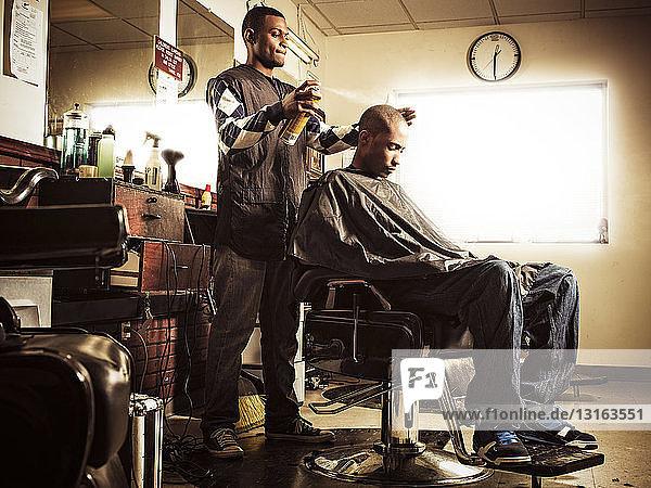Barbier in traditionellem Friseurladen sprüht Haarspray auf Mann