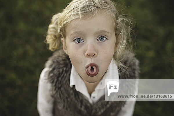 Portrait of young girl  curling tongue