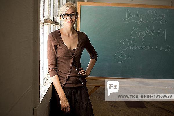 Porträt eines Lehrers mit Hand auf Hüfte und Tafel