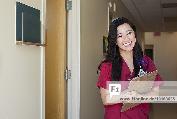 Portrait of young female nurse with clipboard