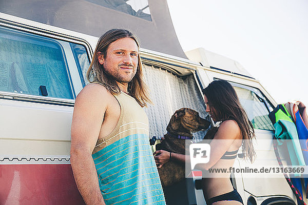 Couple standing beside camper van  pet dog jumping up at woman