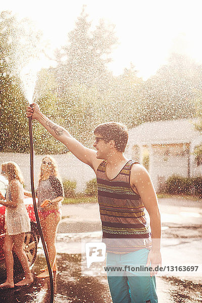 Young man spraying water with hosepipe