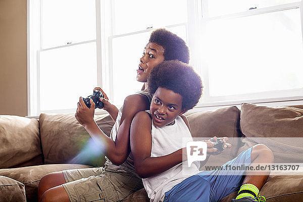 Zwei Brüder Rücken an Rücken beim Spielen von Gamecontrollern im Wohnzimmer