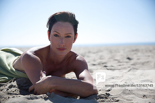 Portrait of mature woman lying on Newport Beach  California  USA
