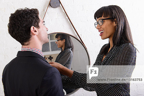 Young woman helping with boyfriend's tie