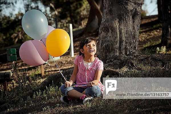 Mädchen auf Gras hält Luftballons
