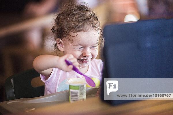 Kleinkind isst Joghurt und benutzt digitale Tablette