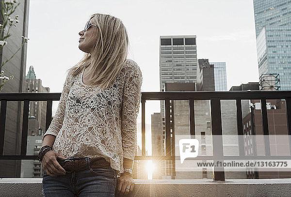 Junge Frau schaut weg mit der Stadt im Hintergrund