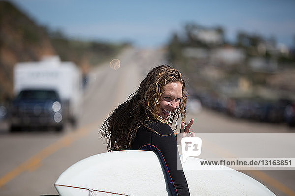 Rear view of young woman carrying surfboard looking over shoulder  sticking tongue out  doing peace sign