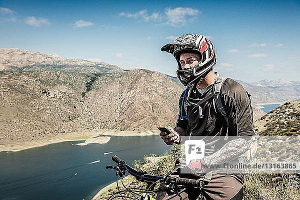 Downhill-Mountainbiker mit Smartphone
