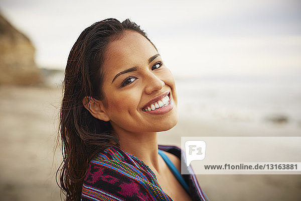Portrait of smiling young woman wrapped in towel on beach  San Diego  California  USA