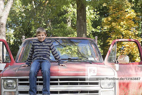 Porträt eines Jungen  der auf der Motorhaube eines Pickup-Trucks im Wald sitzt