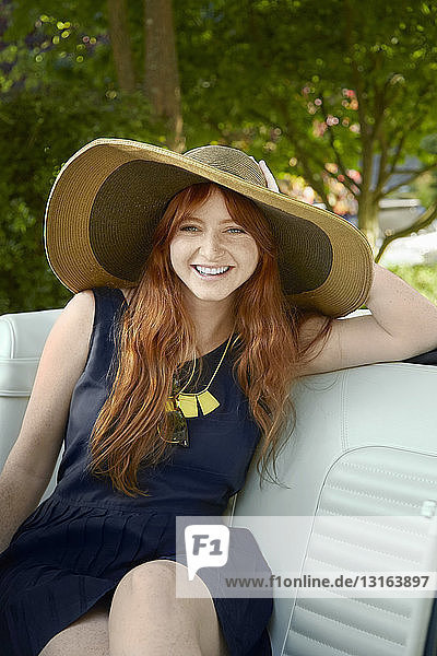 Portrait of young woman with long red hair in back seat of vintage convertible