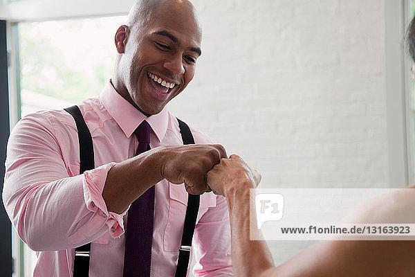 Mittelgroßer erwachsener Mann stößt einen Kollegen mit der Faust und lächelt