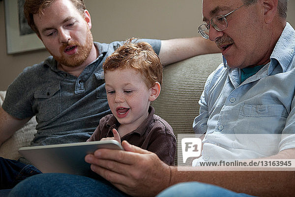 Boy looking at digital tablet with father and grandfather