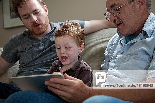 Junge betrachtet digitales Tablett mit Vater und Großvater