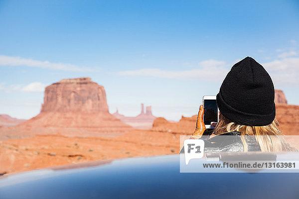 Rückansicht einer mittleren erwachsenen Frau,  die Monument Valley auf einem Smartphone fotografiert,  Utah,  USA