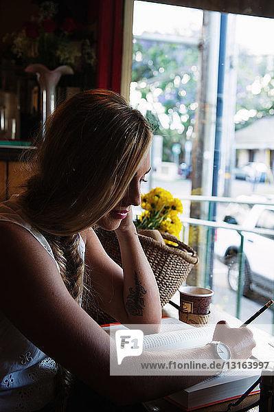 Junge Frau schreibt im Café an einem Buch