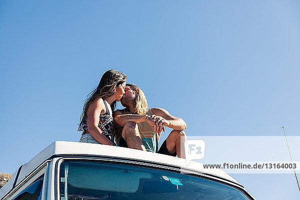 Couple sitting on roof of camper van  kissing