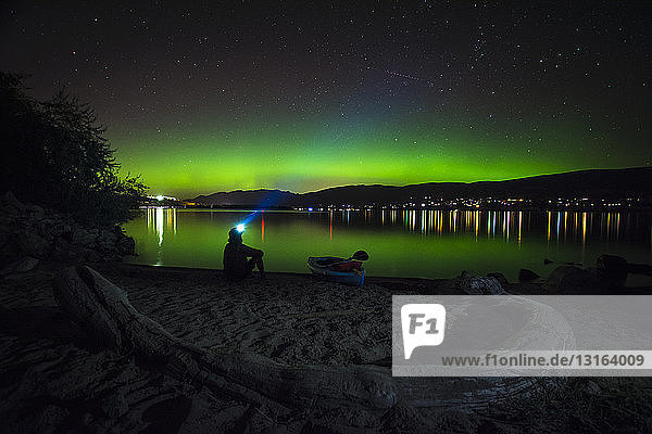 Mann betrachtet Nordlicht über dem Okanagan-See  Kickininee Provincial Park  Penticton  Britisch-Kolumbien  Kanada