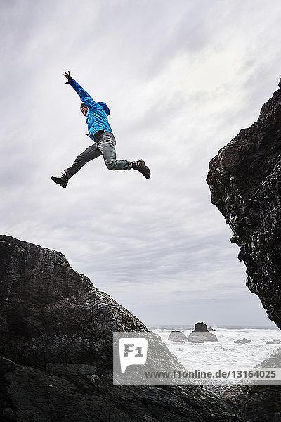 Man leaping over rocks  Prairie Creek Redwoods State Park  California  US