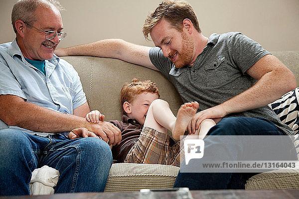 Junge wird von Vater und Großvater gekitzelt