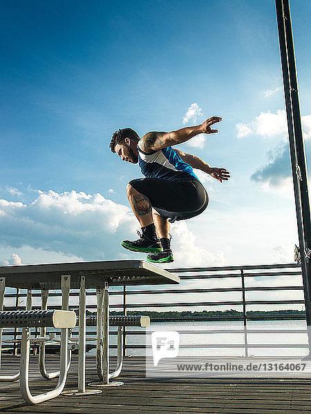 Junger Mann springt rückwärts vom Picknicktisch am Seepier