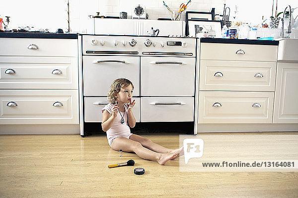 Weibliches Kleinkind sitzt auf dem Küchenboden und spielt mit Lippenstift