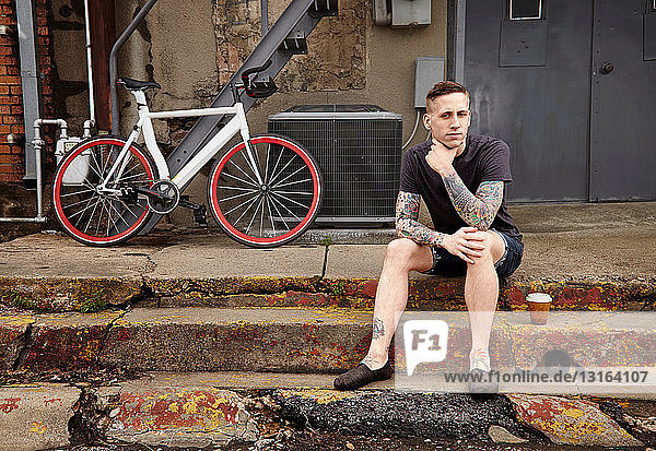 Portrait of young tattooed man on steps