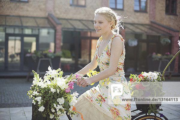 Junge Frau fährt mit dem Fahrrad die Straße entlang und trägt Blumen in Körben auf dem Fahrrad Junge Frau fährt mit dem Fahrrad die Straße entlang und trägt Blumen in Körben auf dem Fahrrad