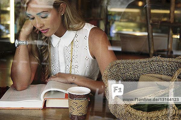 Junge Frau liest im Cafe
