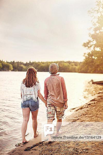 Junges Paar geht am Strand und hält sich an den Händen