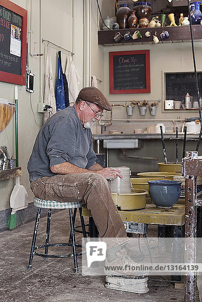 Full length side view of potter in workshop sitting at pottery wheel shaping clay pot