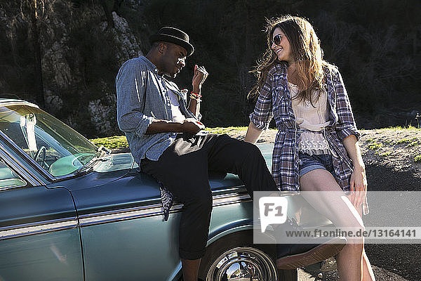Couple sitting and leaning against vintage car