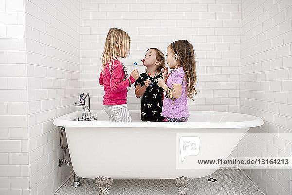 Drei junge Mädchen stehen mit Lutschern in der Badewanne