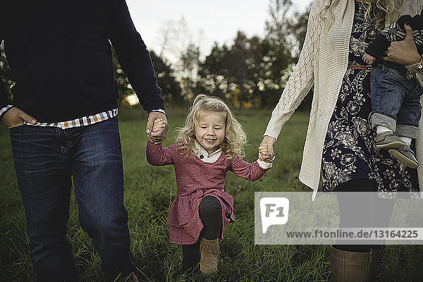 Cropped shot of mid adult couple strolling with daughter and baby boy