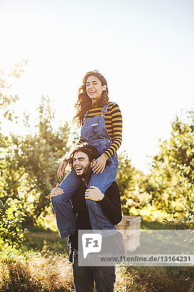 Young couple in rural environment  young woman sitting on man's shoulders  laughing