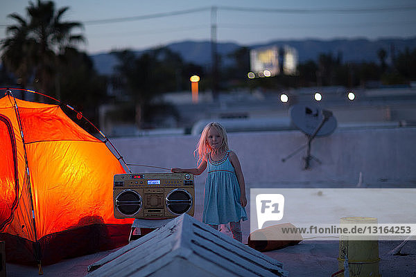 Girl next to illuminated orange colour tent with boombox  looking at camera