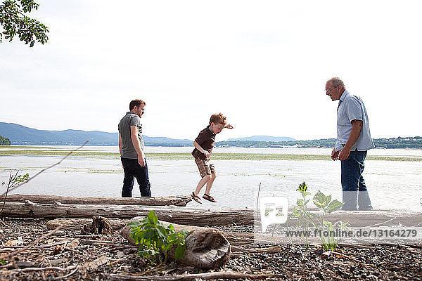 Junge spielt mit Vater und Großvater am Fluss