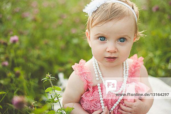Portrait of blue eyed baby girl in meadow