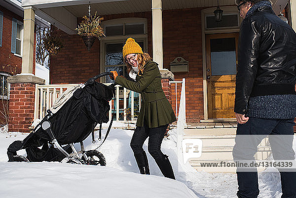 Couple with baby carriage in winter