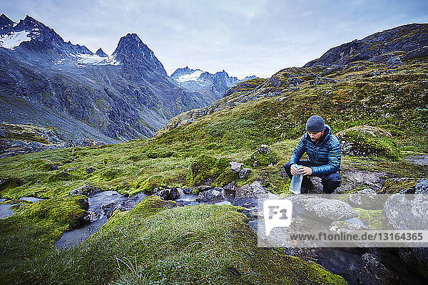 Male hiker filling water bottle from stream  Palmer  Alaska  USA