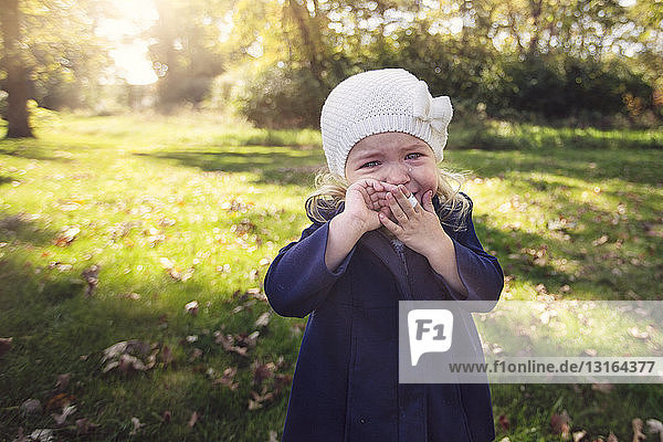 Girl wearing knit hat with adhesive plaster on finger hand to mouth crying