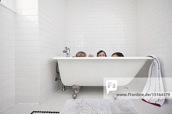 Drei junge Mädchen spähen über Bad