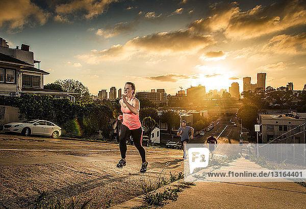Team von Läufern läuft einen steilen Stadthügel hinauf