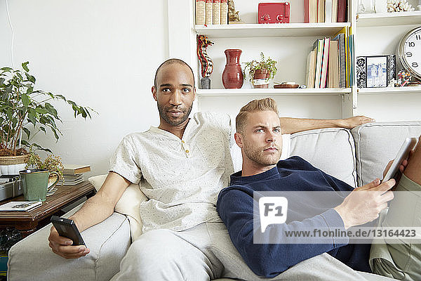 Homosexual couple relaxing together on sofa looking away